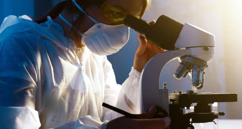 researcher at microscope